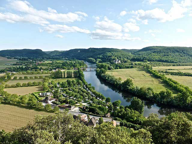 Dordogne river with a bridge and hills in distance