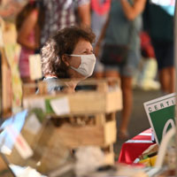 Market stall holder in face mask